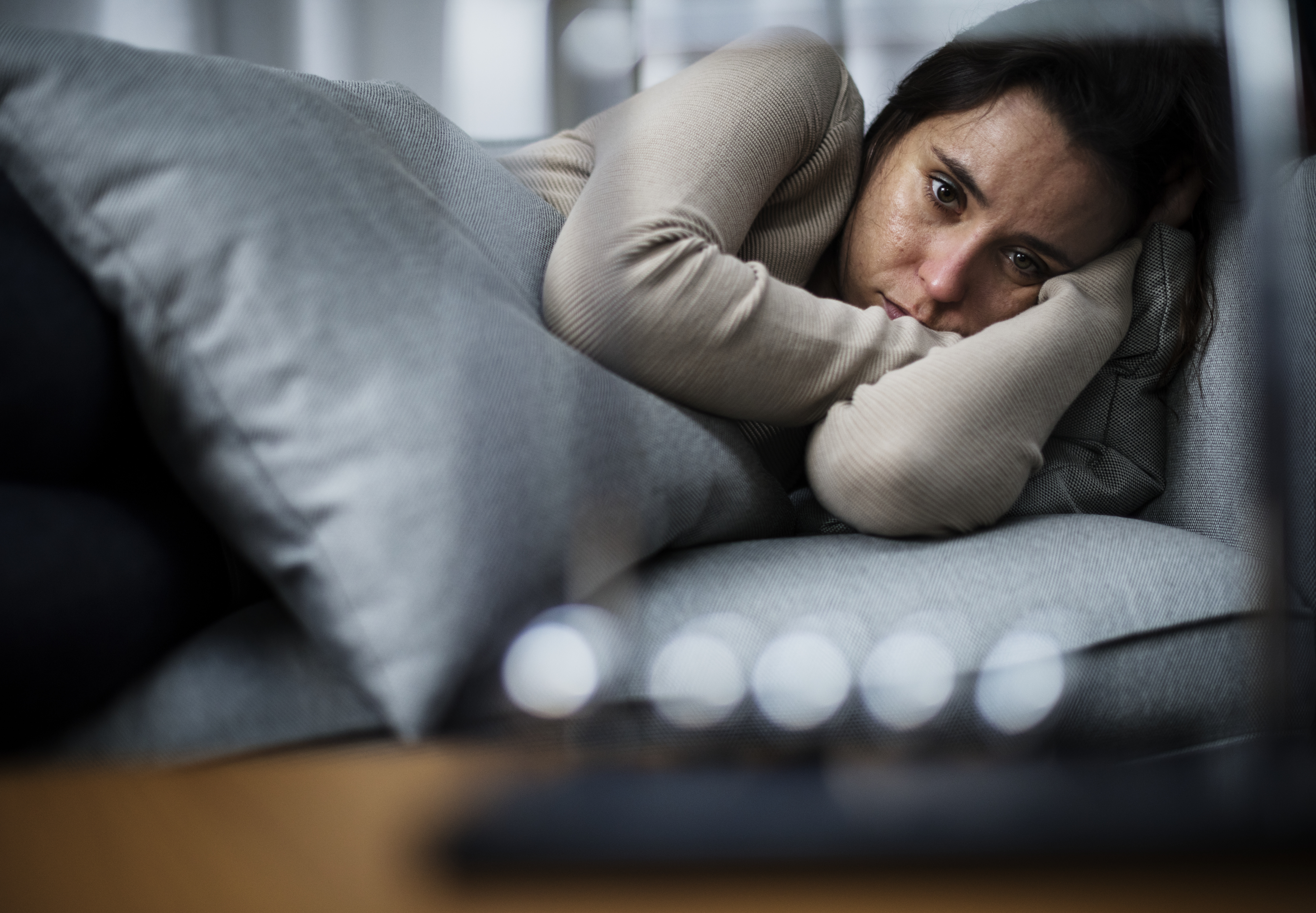woman lying on couch looking distraught