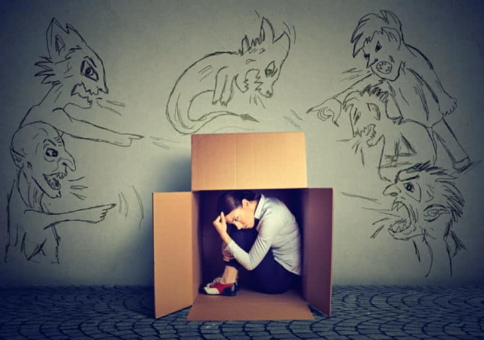 woman hiding in box, sketchings of demons on the wall behind box