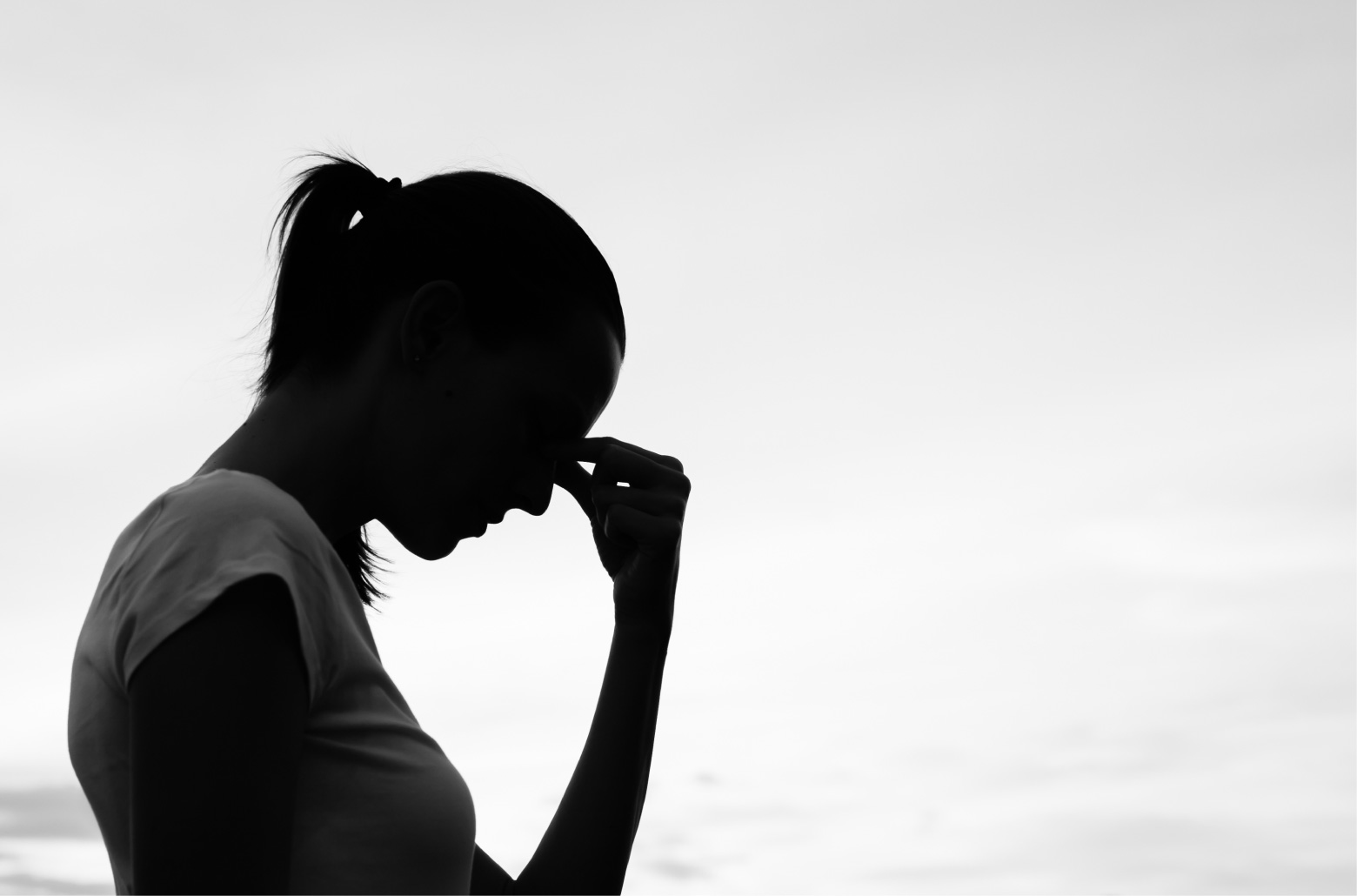 black and white profile of woman holding bridge of nose in pain